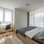 Spálňa v neutrálnych farbách, s drevenou posteľou a pracovným stolom