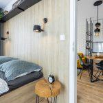 Spálňa s drevenou posteľou, dreveným svetlým obkladom a stolíkmi z drevenej guľatiny, kuchyňa v industriálnom štýle