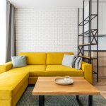 Industriálna obývačka so žltou sedačkou, dreveným stolíkom na kovových nohách, vzorovaným kobercom a bielou tehlovou stenou