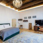 spálňa so starožitným stolom a stoličkou, posteľou s damaskovými obliečkami, tkaným kobercom, krištáľovým lustrom a stropnými drevenými trámami
