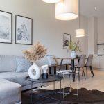 obývačka s kuchyňou: sivá sedačka, hnedá zvieracia koža, kovové okrúhle stolíky, jedálenský stôl a stoličky s čiernymi kovovými podnožami, biely kuchynská linka