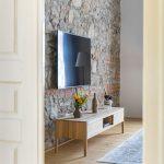 stena v spálni s priznaným kameňom a tehlami, na ktorej visí televízor