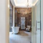 Extravagantná kúpeľňa s presklenými stenami s barokovou vaňou na zlatých nožičkách, mramorovým obkladom, kreslom a rebríkovým radiátorom