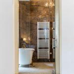 kúpeľňa s barokovou vaňou na zlatých nožičkách, mramorovým obkladom, rebríkovým radiátorom a presklenými stenami