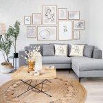 obývačka so sivou rohovou sedačkou, jutovým pleteným kobercom, prírodným vypletaným konferenčným stolíkom, a bielou tehlovou stenou s obrazmi