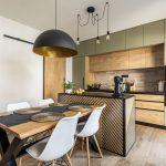industriálne ladená kuchyňa s kuchynskou linkou v drevodekore a olivovo zelenej farbe so zástenou imitujúcej tehlu, s kuchynským ostrovčekom s potlačou rybej kosti, na ktorý nadväzuje jedálenský stôl s podnožou X a výraznou čiernou lampou so zlatým vnútrom