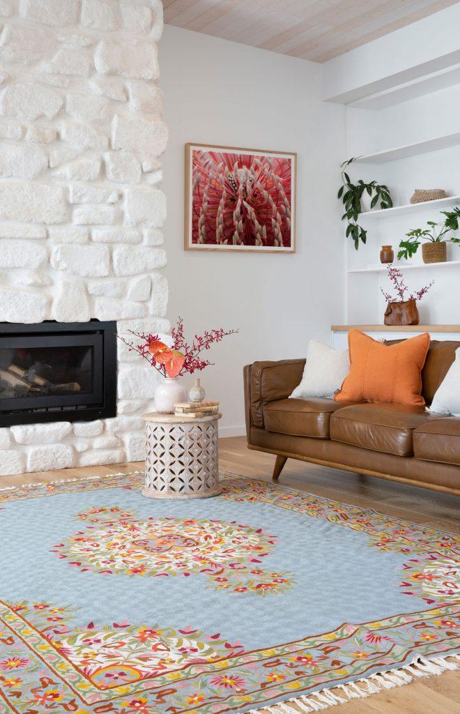 Obývačka s hnedou sedačkou, tkaným kobercom s kvetinovým vzorom a krbom obloženým bielym kameňom