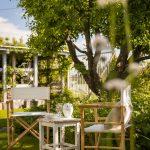 vidiecke stoličky so stolčekom umiestnené v tieni stromu v okrasnej záhrade