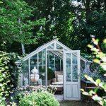 presklený záhradný domček zariadený nábytkom, ktorý môže slúžiť aj ako skleník