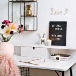 Biely pracovný stôl s kovovými policami zavesenými na stene