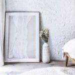 detail interiéru s bielou tehlovou stenou, opretým abstraktným obrazom, bielou keramickou vázou s kvetmi a pleteným kobercom