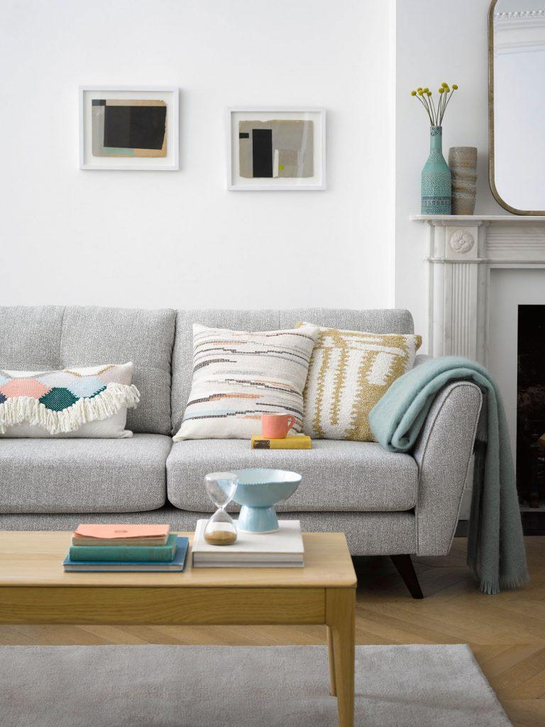 obývačka v pastelových farbách, so sivou sedačkou, vankúšmi a jednoduchým dreveným stolíkom