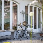 záhradná terasa pri rodinnom dome s kovovým stolíkom a lavičkami vyrobenými zo zvyškového materiálu po stavbe prístrešku na drevo