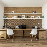pracovňa v dreve, so stolom po celej dĺžke steny, otvorenými policami a dreveným obkladom na stene s potlačeným vzorom rybej kosti