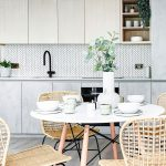 Kuchyňa v neutrálnych tónoch s bielym jedálenským stolom, prírodnými vypletanými stoličkami, kuchynskou linkou v betónovom vzhľade a obkladom na zástene so vzorom rybacej kosti