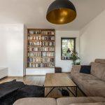 industriálne ladená obývačka so sivohnedou sedačkou, stolíkom s kovovou podnožou, kravskou kožou a otvorenou knižnicou vo výklenku