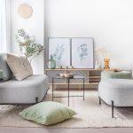 harmonický interiér vo farbách zelenej, sivej a hnedej, so sivými kresielkami, smotanovými a svetlozelenými doplnkami a drevenou skrinkou na nožičkách