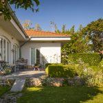 rodinný som so žulovou terasou so sedením, suchým múrikom, tvarovanými krušpánmi, bielymi cesnakmi a trvalkami