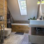 podkrovná industriálna kúpeľňa v dekóre dreva, s imitáciou betónu a patchworkovou podlahou a obkladačkami