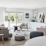 škandinávska obývačka so sivou sedačkou a kreslom, staroružovým kreslom, dreveným obkladom na stenách a obrazmi opretými o steny