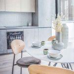 kuchynská linka v dekóre dyhy a betónu, so zástenou z obkladov vo vzore rybej kosti a jedálenský stôl so stoličkami so zamatovým čalúnením