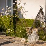 Detail dekorácie v okrasnej záhrade s drôtenou sliepkou a vtáčou klietkou