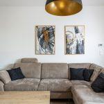 interiér so sedačkou v tvare L, obrazmi, konferenčným stolíkom a lustrom so zlatým vnútrom tienidla