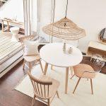 Jednoduchý jedálenský kút so stolom a stoličkami oživený ratanovým tienidlom na lustri