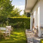 rodinný dom s vidieckou romantickou záhradou, so žulovou terasou, trvalkovými záhonmi s bielo kvitnúcimi kvetmi a drevenými stoličkami so stolíkom