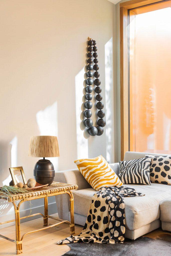 interiér zariadený na africký štýl, so sivou sedačkou s vankúšmi so zvieracími vzormi, stolíkom a nástennou dekoráciou v podobe nadrozmerného dreveného náhrdelníku