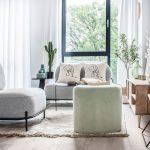 svetlý interiér so sivými kreslami, svetlozelenou taburetkou, smotanovým kobercom a drevenou skrinkou