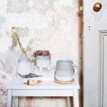 zátišie so stolíkom, keramickou vázou, kvetináčom a hrnčekom vo vidieckom štýle a so stenou s ošarpaným vzhľadom