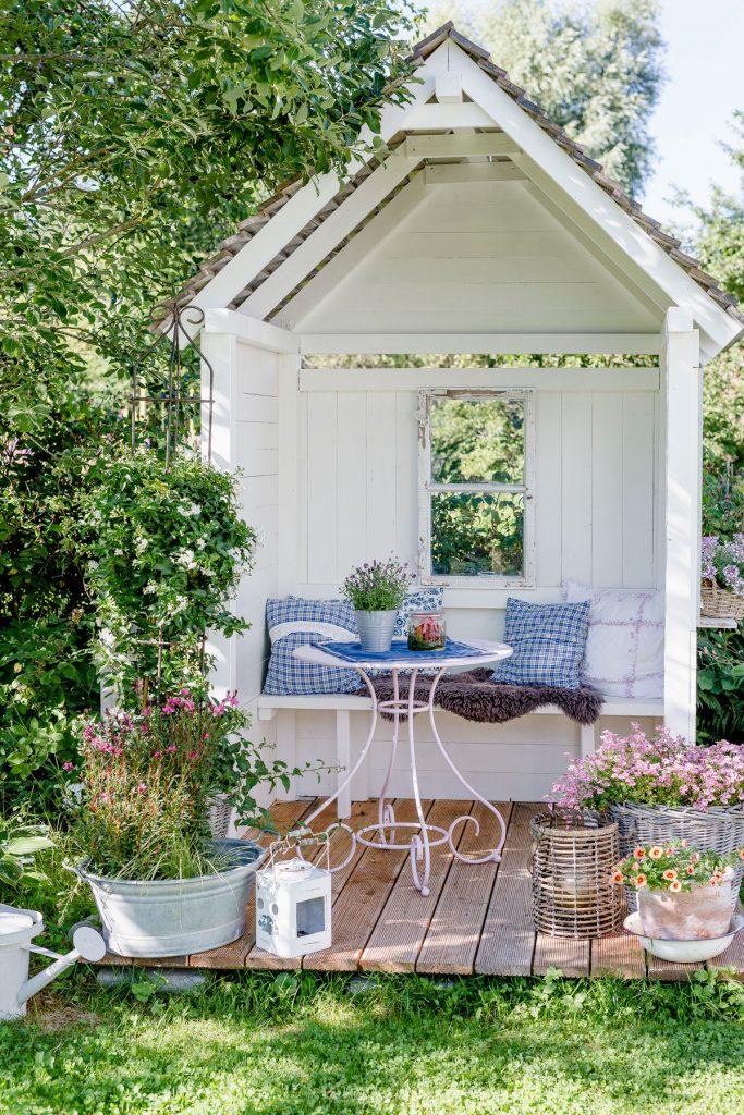 romantický biely záhradný prístrešok s terasou a kvetinami