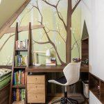 pracovný kút v podkrovnej detskej izbe s dreveným nábytkom a tapetou s motívom stromov