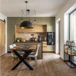Industriálna kuchyňa s olivovo zelenou kuchynskou linkou, ostrovčekom s potlačeným vzorom rybej kosti, jedálenským stolom s čiernym lustrom a posuvnými dverami vedúcimi do komory