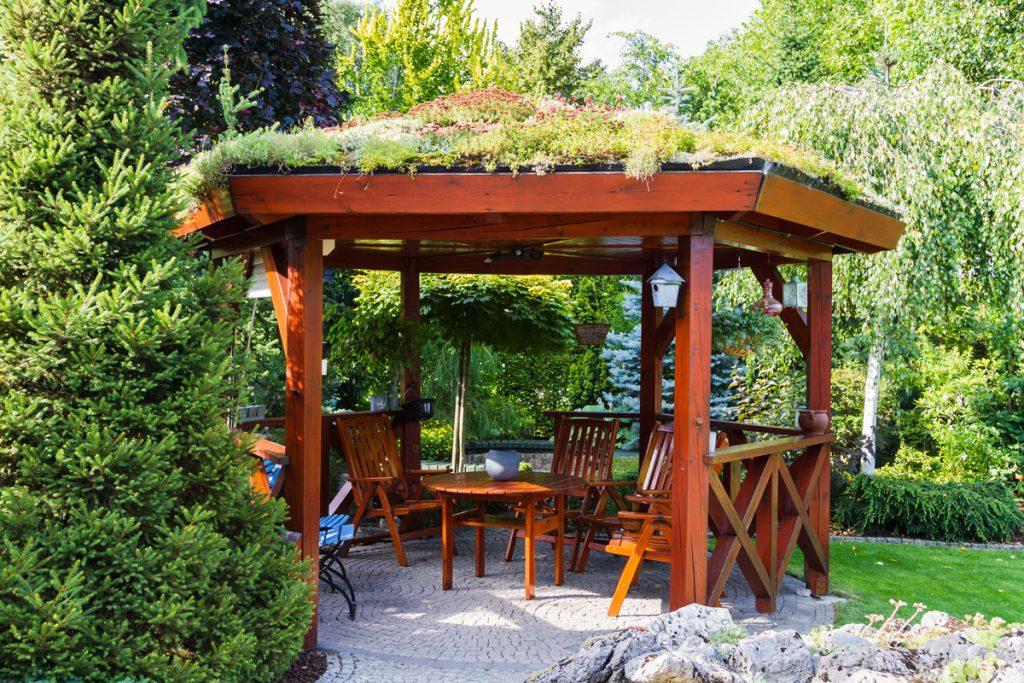 Drevený altánok so zelenou strechou