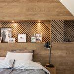 spálňa v drevodekóre s guľatinou slúžiacou ako stolík na lampu a obloženou drevenou stenou s výklenkom so vzorom rybej kosti