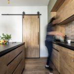 industriálna kuchyňa v drevodekore s posuvnými dverami - barn doors vedúcimi do komory, ostrovčekom a kuchynskou linkou
