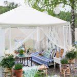 biely altánok zariadený ako obývačka s pohovkou, lavicou, stolíkom, kobercom a kvetinami