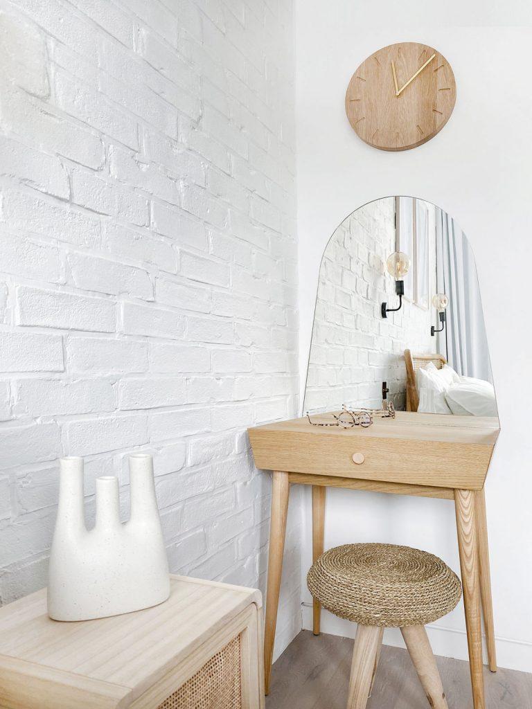 detail spálne s tehlovou stenou, dreveným nočným stolíkom s vypletanými dvierkami a toaletným dreveným stolíkom s oblúkovým zrkadlom a vypletanou trojnožkou