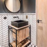 menšia kúpeľňa v industriálnom štýle v kombinácii hnedej a čiernej farby, s obkladom vzoru rybej kosti a podlahou s 3D efektom kociek
