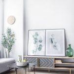 detail obývačky v prírodnom štýle s jutovým pleteným kobercom, konferenčným stolíkom, a skrinkou s obrazmi opretými o stenu