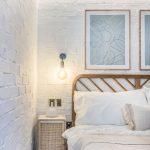 detail spálne v prírodnom štýle ladenej tón v tóne, s drevenou posteľou, nočným stolíkom s vypletanými dvierkami a bielou tehlovou stenou