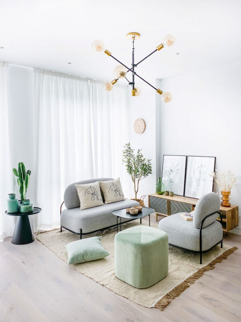 obývačka so sivými kreslami, zelenou taburetkou, prírodným kobercom, skrinkou, čiernym stolíkom s dekoráciami a viacramenným lustrom v čierno-zlatej kombinácii