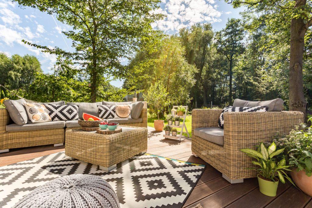 Terasa so záhradným sedením obklopená stromami
