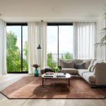 Elegantná a moderná obývačka so svetlou sedačkou, hnedým kobercom a originálnym dizajnovým stolíkom v tvare presýpacích hodín