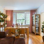 Obývačka spojená s jedálňou s dreveným stolom, presklenou vitrínou s riadmi a nástennými otvorenými policami a kvetináčmi vyrobenými na mieru z dreva