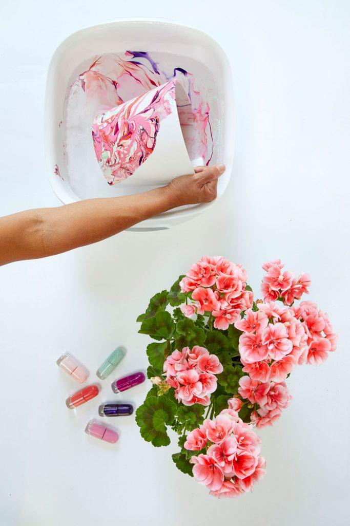 zdobenie bieleho keramického kvetináča pomocou ponárania do vody, na ktorej hladine sú vyliate laky na nechty