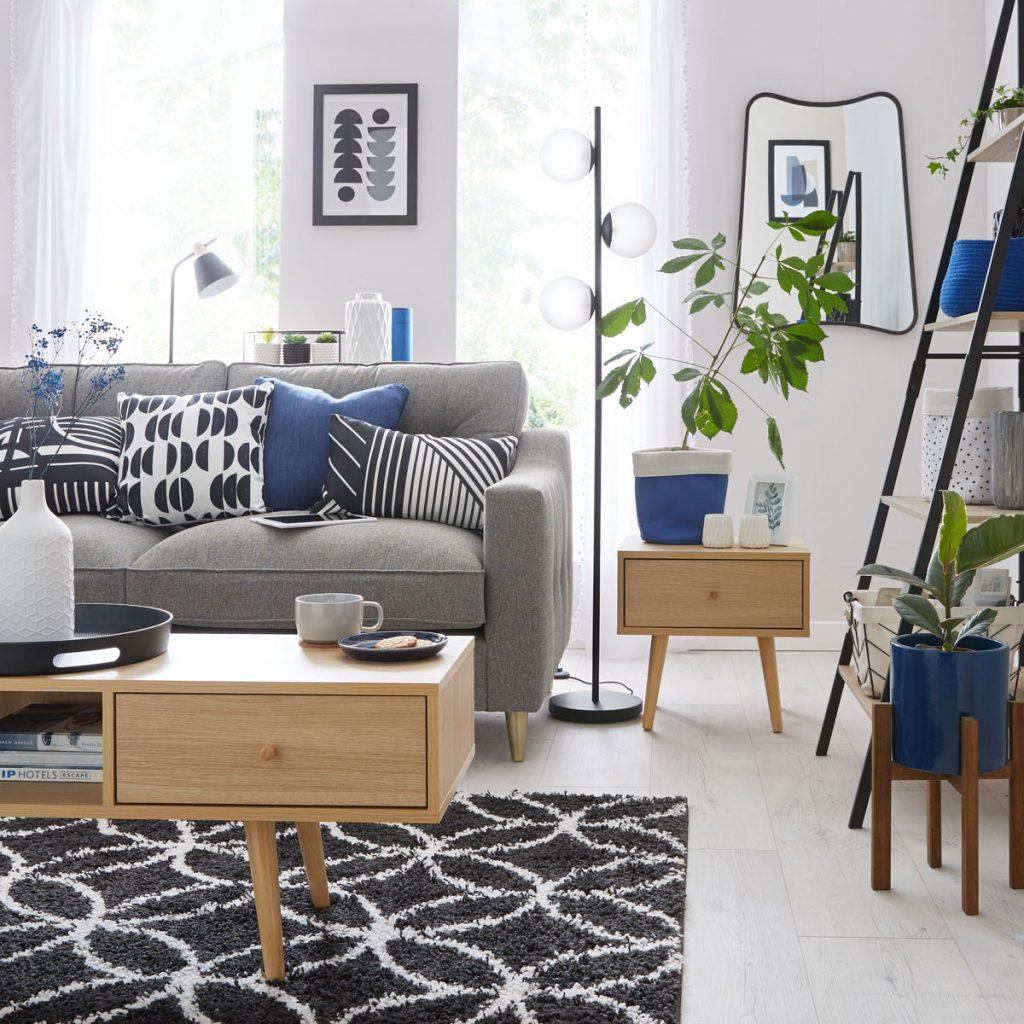 Obývačka so vzorovaným čierno-bielym kobercom, dreveným stolíkom a sivou sedačkou so vzorovanými vankúšmi