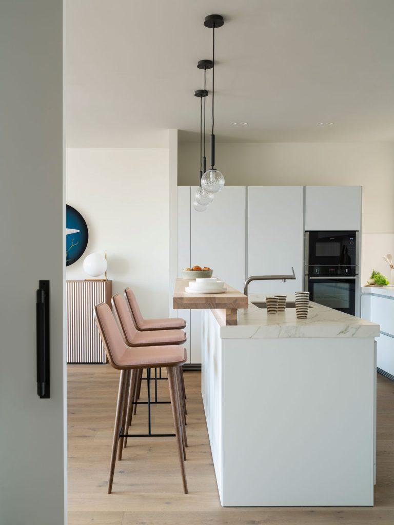moderná kuchyňa s bielou kuchynskou linkou a ostrovčekom s barovým stolíkom a zaoblenými barovými stoličkami
